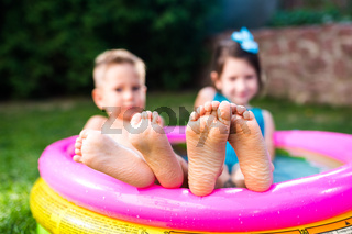 Theme summer vacation. Two children Caucasian brother and sister lie in water, inflatable home round pool in yard on green grass. Close-up of feet sole heels children in hot summer weather