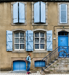 teenage girl dressed in blue interacting with her cell phone in front of a house with blue shutters