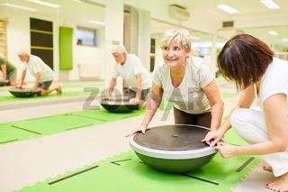 Physiotherapeutin hilft Seniorin beim Fitness Training