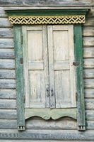 The window of the old house is covered with wooden shutters