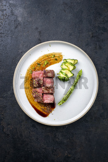 Barbecue dry aged wagyu fillet steak on hot smoked sauce with grilled green asparagus and sliced zucchini as top view on a modern design plate with copy space
