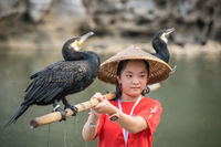 Girl with cormorants in front of The Elephant Trunk Hill Arch