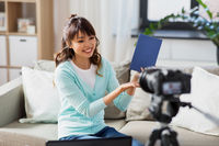 asian female blogger making video review of book