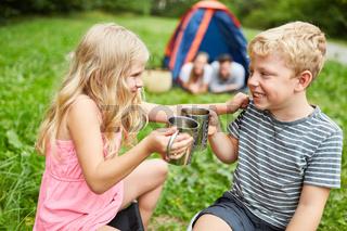 Kinder mit Tassen auf dem Campingplatz