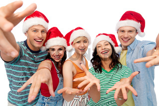 happy friends in santa hats over white background