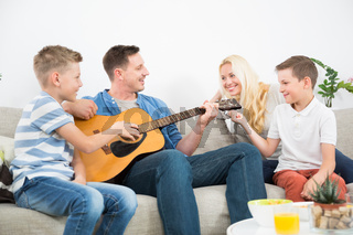 Happy caucasian family smiling, playing guitar and singing songs together at cosy modern home