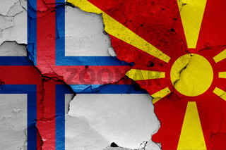flags of Faroe Islands and North Macedonia painted on cracked wall