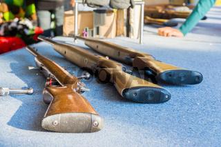 Three Air Rifles Laying Table Fair Game Blue Texture