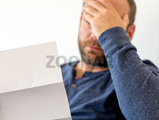 man reacting to bad news he receives in a letter selective focus