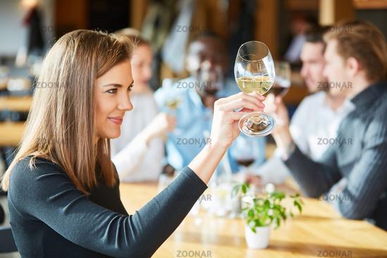 Junge Frau auf einem Weinseminar mit einem Glas