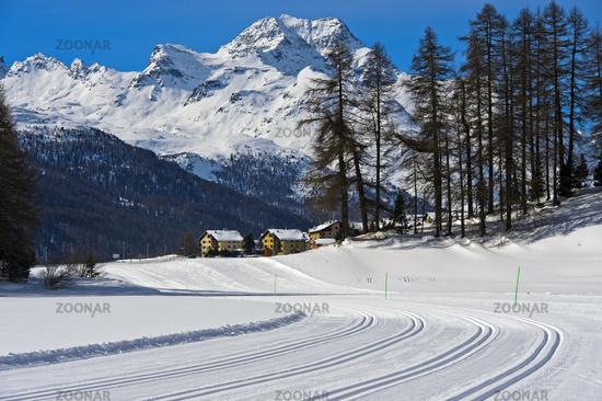 Cross-country skiing trails on the frozen lake Champfersee, peak Gipfel Piz de la Margna,Switzerland