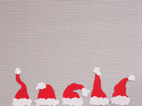 Five handmade hats of Santa on a paper background