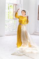 Model in a Yellow Dress Posing in a Photo Studio.