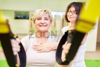 Seniorin bei Schlingentraining in Physiotherapie