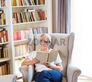 Seniorin beim Buch lesen in ihrer Seniorenwohnung