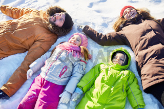 Happy family lying in snow