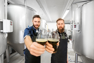 brewers clinking glasses of craft beer at brewery