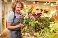 Florist beim Blumen binden mit Rosen