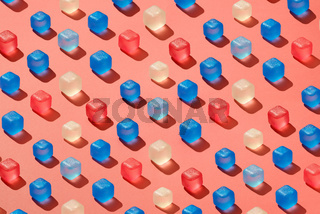 Diagonal rows pattern from colored plastic ice cubes on a background in a trend color of the year 2019 Living Coral Pantone.