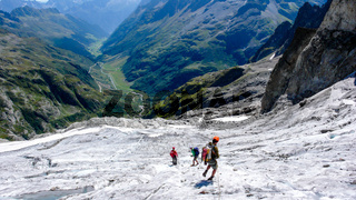 group of male mountain climbers crossing a glacier on their way down from a high alpine peak