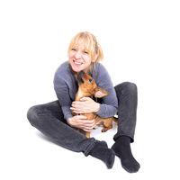 Blonde woman sitting on the floor with her tiny brown dog isolated on white background in the studio.  Small mixed breed of jack russell terrier, german shepherd and chihuahua. Age 2 years.