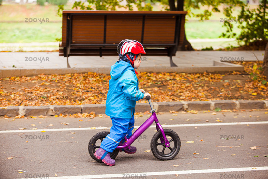 Three years boy is riding on balance bike at the cycle track