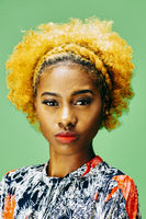 Vertical portrait of a lovely young girl with bleached curly hair, in front of a green background