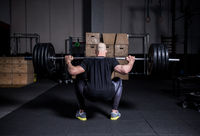 Athletic Muscular Man Lifting Weights and Doing Back Squat in Gym. Dramatic Color Grading.