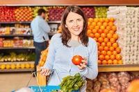 Frau hält eine gesunde Bio Tomate in der Hand