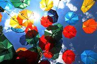 Multicolored umbrellas. Colorful umbrellas flying in the summer blue sky.
