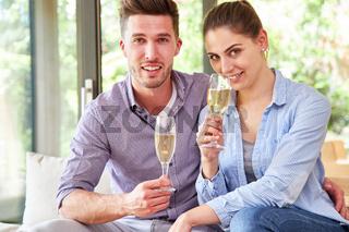Glückliches junges Paar trinkt ein Glas Sekt