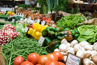 market stand with many different vegetables and labels with names and prices in French