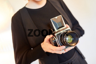 Fotograf hält Mittelformatkamera oder Schachtkamera