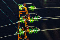 High voltage power tower detail with set of glass electrical insulators view from above