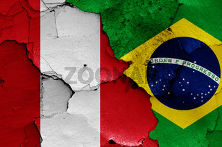 flags of Peru and Brazil painted on cracked wall
