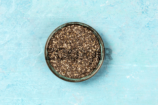A bowl of chia seeds, shot from the top on a blue background with a place for text