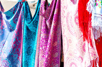 Closeup of colorful Portuguese fabrics and shawls in turquoise, pink and purple colors