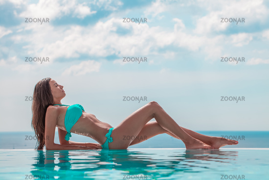 Woman resting at infinity pool