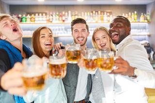 Gruppe Freunde feiert ausgelassen in einer Kneipe