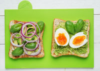 Two avocado toasts on green background