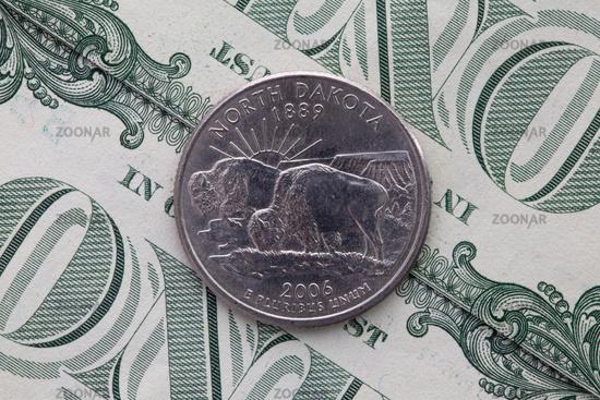 Symmetric composition of US dollar bills and a quarter of North Dakota.
