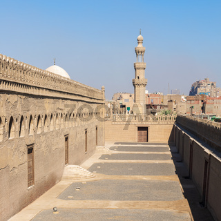 Passages outside Ibn Tulun mosque with the minaret of Amir Sarghatmish mosque at far distance, Cairo, Egypt