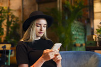 Blond girl in white jeans skirt, blouse and black hat, sitting at cafe table by the window alone, looking  at the mobile phone
