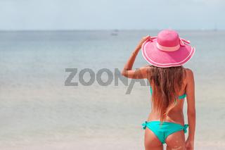 Woman in sunhat and bikini standing on beach