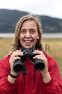 young blonde woman hiking and watching through binoculars.