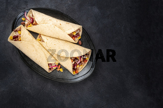 Burrito sandwich wraps, shot from above on a black background. Tortillas stuffed with ground beef meat, rice, beans, onions, and chili peppers, with a place for text