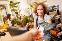 Hand gibt Kreditkarte zum Bezahlen an der Kasse