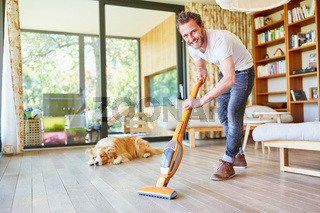 Hausmann beim Parkett Boden staubsaugen