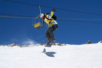 Snowboarder jumping on snowy ski slope
