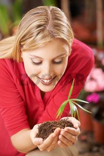 Frau hält kleine Pflanze in den Händen